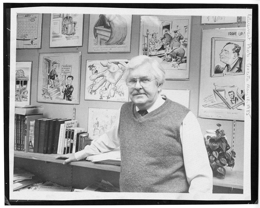 Retirement portrait of Bill Graham standing in front of political cartoons. 1985.